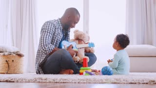 Young black father playing ukulele with son in sitting room