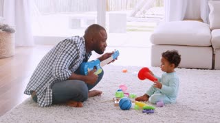 Young black father playing with his son in sitting room