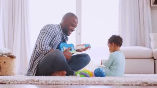 Young black father playing with son in their sitting room