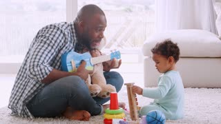 Young black father singing to his crying son in sitting room
