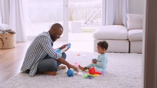 Young black father singing to his young son in sitting room