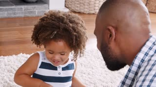 Young black girl playing instrument with dad in sitting room