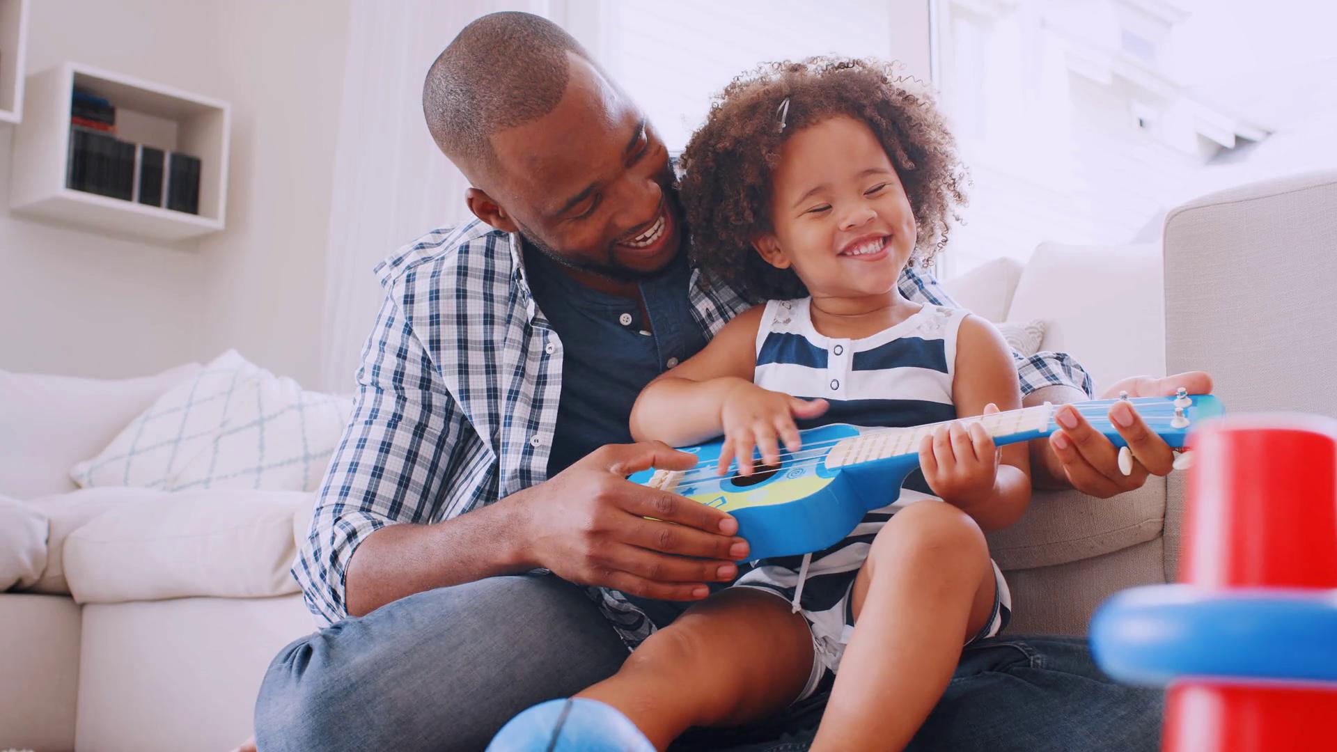 Young black girl sitting on dad's knee playing ukulele Stock Video Footage  - Storyblocks