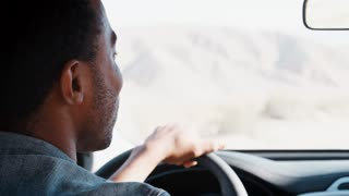 Young black man driving car and talking, over shoulder view