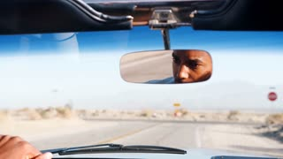 Young black man driving open car, seen in rear view mirror