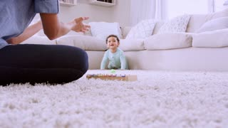 Young black woman playing with crawling toddler, low angle
