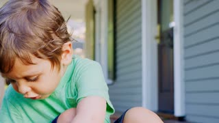 Young Boy Sits On Porch Of House Playing With Toys