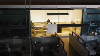 Young businesswoman working in empty office, elevated view