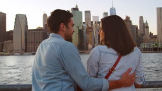 Young couple talking by the river in Manhattan, back view