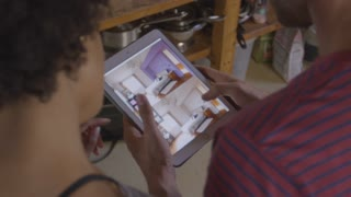 Young couple using tablet computer, over shoulder view, shot on R3D