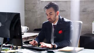 Young Hispanic businessman using phone in his office