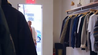 Young Hispanic couple looking at clothes in a clothes shop