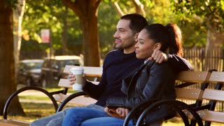 Young Hispanic couple sit talking on bench in Brooklyn park
