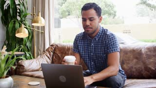 Young Hispanic man using laptop at a coffee shop