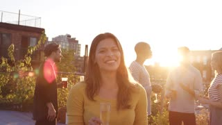 Young Hispanic woman at a rooftop party smiling to camera