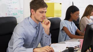 Young man and woman discussing document in open plan office