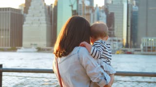 Young mother with daughter standing at riverside, Manhattan