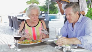 Waiter Serving Pizza To Senior Couple In Outdoor Restaurant
