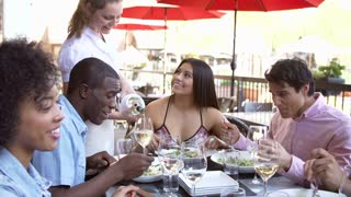 Waitress Pouring Wine For Group Of Friends At Restaurant