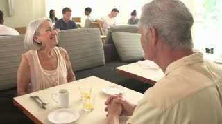 Waitress Serving Senior Couple Breakfast In Hotel Restaurant