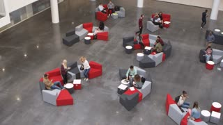 Wide overhead shot of students in a busy university lobby, shot on R3D
