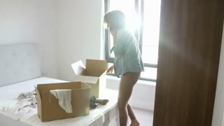 Woman Moving Into New Home Talking On Mobile Phone