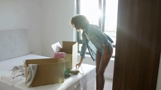 Woman Moving Into New Home Unpacking Clothes In Bedroom