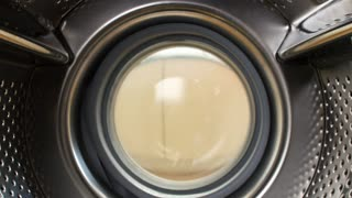 Woman Putting Laundry Into Washing Machine