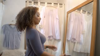 Woman taking selfie in a boutique changing room