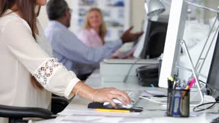 Woman Using Computer At Desk In Busy Creative