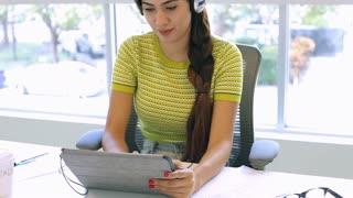 Woman Using Digital Tablet And Headphones In Design Studio