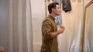 Woman watches her partner trying on shirt in changing room