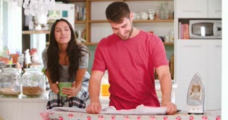 Woman Watching Man Ironing Shirt In Kitchen