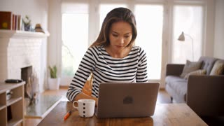 Woman Working From Home Using Laptop On Dining Table