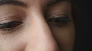 Woman�s brown eyes moving, and creasing to smile, side view