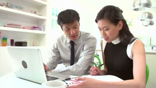 Worried Asian Couple Looking At Personal Finances