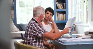 Worried Mature Couple In Home Office Looking At Paperwork