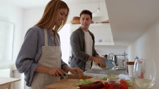 Young adult couple talking as they prepare food and wash up, shot on R3D