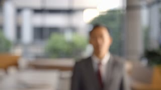 Young Asian businessman walking into focal plane