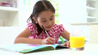 Young Asian Girl Doing Homework Seated At Table