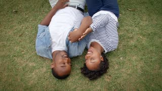 Young black couple lying on grass together, shot from above