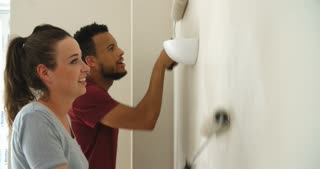 Young couple decorating home with paint rollers, close up