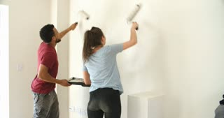 Young couple decorating home with paint rollers