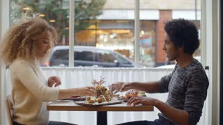 Young Couple Enjoying Meal On Date In City Restaurant