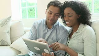 Young Couple Making Online Purchase Using Digital Tablet