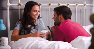 Young Couple Relaxing In Bed With Hot Drink
