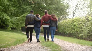 Young couples walk and piggyback in country lane, back view