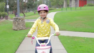 Young Girl Riding Bike In Park Looking At Camera