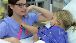 Young Girl Talking To Female Nurse In Intensive Care Unit