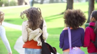 Young Girls Running In Slow Motion Away From Camera In Park